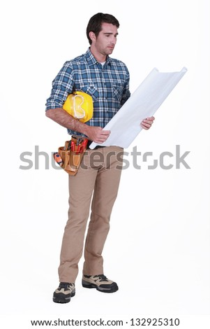 Construction foreman looking at a blueprint - stock photo
