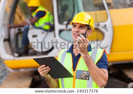 construction foreman talking on walkie-talkie holding clipboard - stock photo