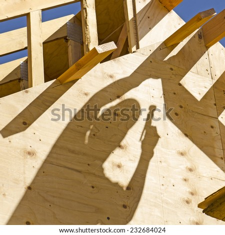 Construction framing contractor carpenter building out the gable end of the roof with purlin and fascia trim boards - stock photo