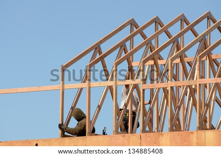 Construction framing contractor installing the roof truss system to a new commercial residential development - stock photo