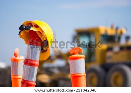 Construction hard hat on road pilon - stock photo