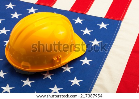 Construction helmet laying over USA flag - closeup shoot - stock photo