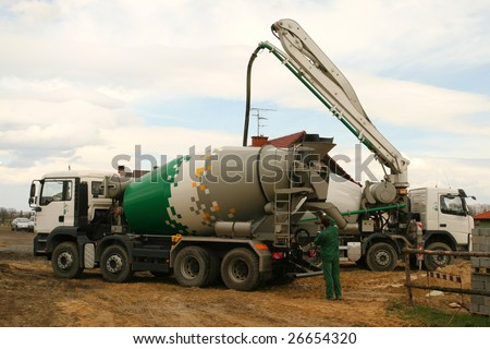 Construction industry machinery. Concrete mixer truck and a worker. - stock photo