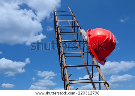 Construction industry still life with hardhat hanging on steel bars against blue sky - stock photo
