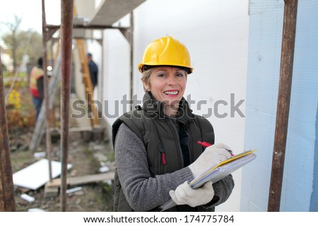 Construction inspector examine styrofoam insulation of house facade - stock photo