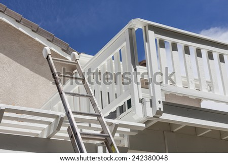 Construction Ladder Leaning on White House Deck with Blue Sky Behind.. - stock photo