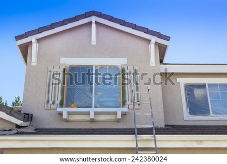 Construction Ladder Leaning Up Against A House Ready For New Paint. - stock photo