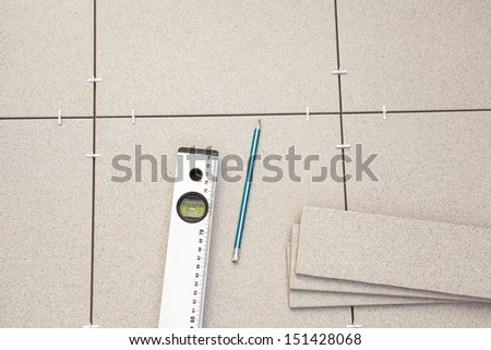 Construction level with pencil laying on tiles on the floor - stock photo
