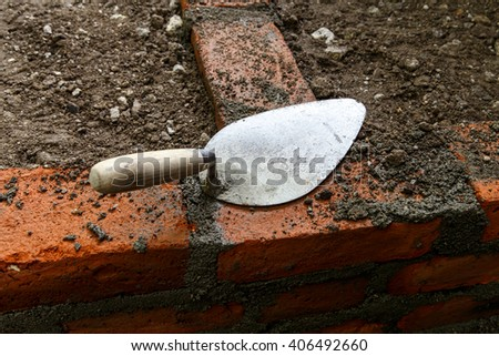 construction lute trowels in a brick wall - stock photo