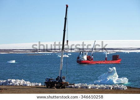Construction machinery in Arctic with icebergs background