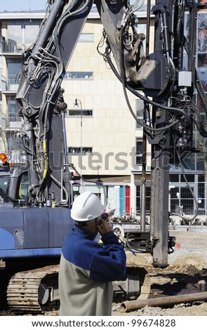 construction machinery, workers and building site, bulldozers and diggers - stock photo