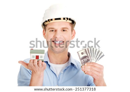 Construction man holding house model and money. - stock photo