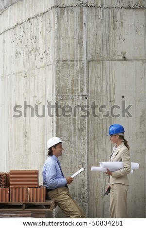 Construction manager and architect talking on site - stock photo