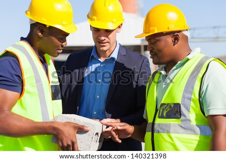 construction manager and two workers examining a brick - stock photo