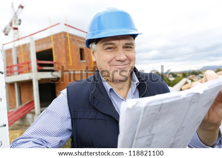 Construction manager checking building project on site - stock photo