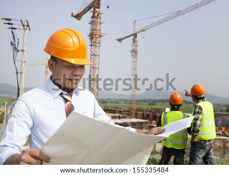 Construction manager checking plans  building project on site - stock photo