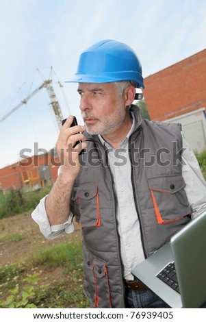 Construction manager on building site with laptop computer - stock photo