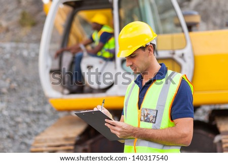 construction manager writing report at construction site - stock photo