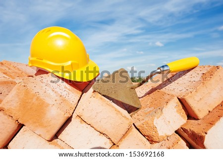 construction mason work tools. Brick trowel and hardhat outdoors at building area - stock photo