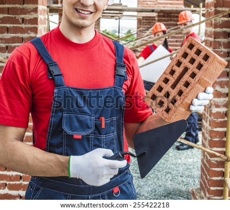 construction mason worker bricklayer hold in hand red brick with trowel putty knife outdoors wear white gloves and blue cotton material overall against two engineer with blueprint paper plan  - stock photo