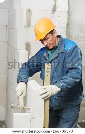 construction mason worker bricklayer inspecting with level installation of calcium silicate brick during indoor wall creation - stock photo