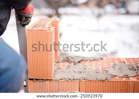 construction mason worker bricklayer installing brick walls with trowel putty knife outdoors during winter - stock photo