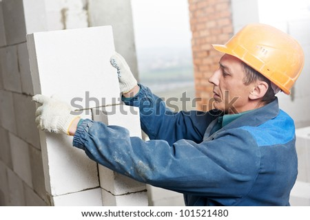 construction mason worker bricklayer installing calcium silicate brick during indoor wall creation - stock photo