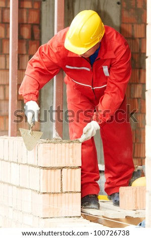 construction mason worker bricklayer making a brickwork with trowel and cement mortar - stock photo