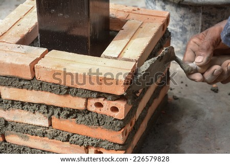 Construction mason worker with trowel and cement mortar - stock photo