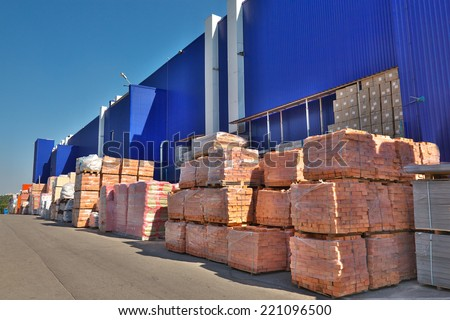 Construction materials stacked near the warehouse - stock photo