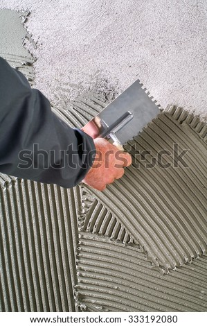 Construction notched trowel with grey cement mortar for tiles work - stock photo