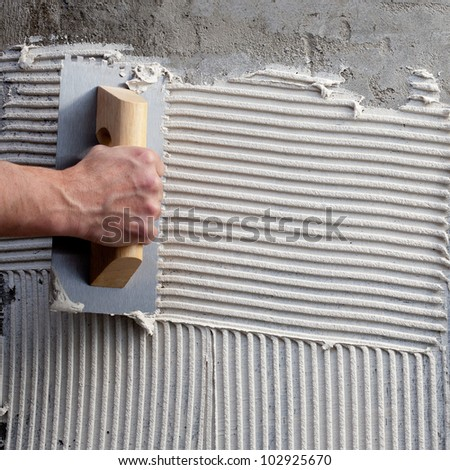 construction notched trowel with white cement mortar for tiles work - stock photo