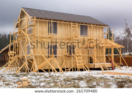 construction of a frame house in scaffolding with snow - stock photo