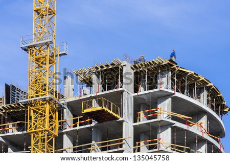 Construction of a house with a yellow tower crane on blue sky background - stock photo