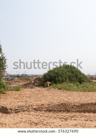 Construction of a new road in the new residential area, a lot of sand and a large green hill with wild grass, Moscow Oblast Russia - stock photo