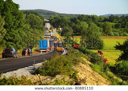Construction of a new road leading to a distant city - stock photo