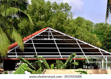Construction of aluminium roof on the terrace of a house in Trivandrum, Kerala, India. Geometric lines, shapes and patterns. Truss work.  - stock photo