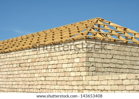 Construction of brick limestone, wood roof frame on the background of sky.