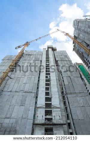 Construction of building with cranes as seen from below - stock photo