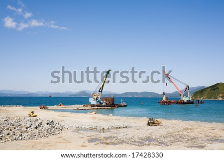 Construction of new seaport(oil harbor).Floating cranes. - stock photo