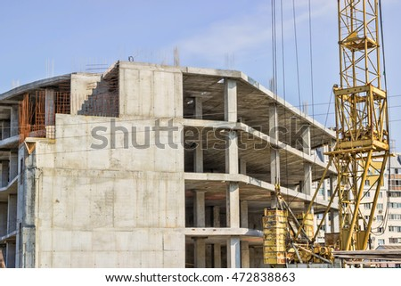 Construction of the building. Hoisting crane on blue sky background.