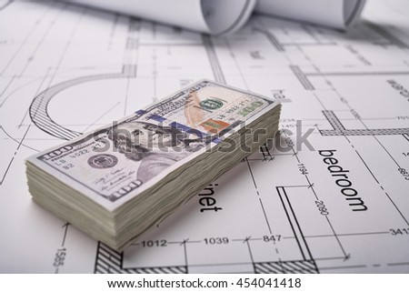 Construction of the building layout, construction financing, packs of dollars, building drawing on paper, drawings rolled in a roll.