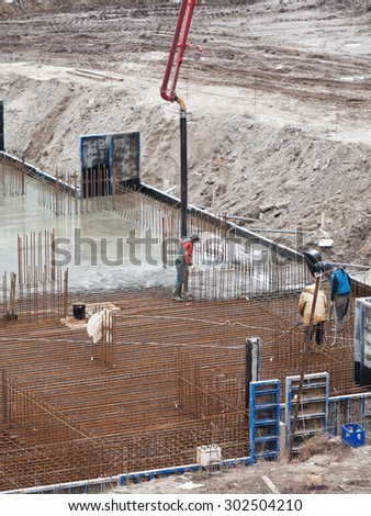 Construction of the building. Pouring the concrete foundation slab foundation. The concrete base slab foundation under the building. Stages of construction of the building.   - stock photo