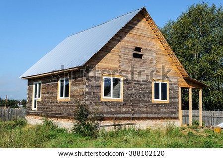 Construction of wooden house with a metal roof in the village, sunny summer day - stock photo