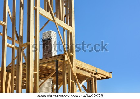 Construction on a house with framework being built around the original chimney - stock photo