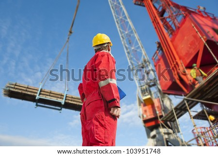 Construction operator looking at a crane carrying scaffolding materials to a super sized structure at a building site - stock photo