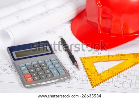 Construction plans with hard hat and drawing tools. Shallow depth of field