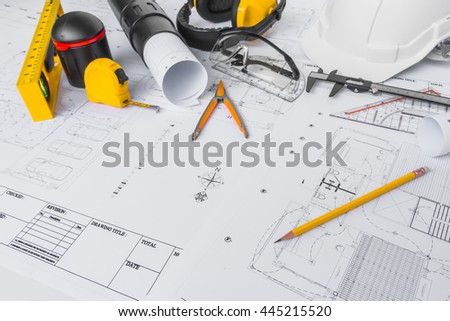 Construction plans with White helmet and drawing tools on blueprints - stock photo