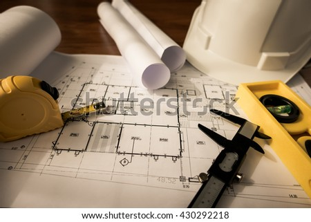 Construction plans with White helmet and drawing tools on blueprints  ( Filtered image processed vintage effect. ) - stock photo