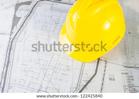 Construction plans with yellow helmet - stock photo